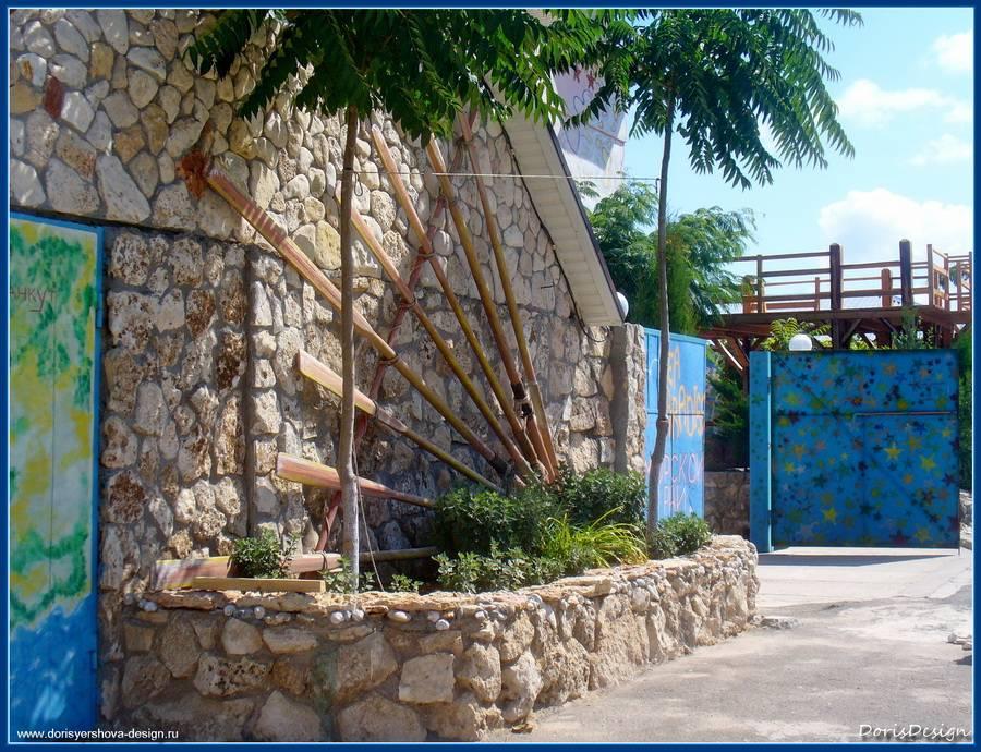 Стена дома с декоративным цветником. Кладка колотым известняком и морской галькой.      Фото - © Дорис Ершова