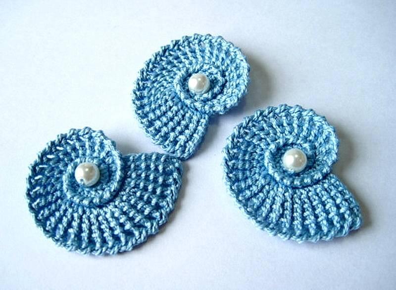 голубые ракушки-улитки связанные крючком. в центре пришита жемчужина